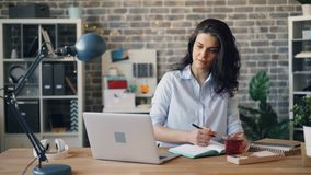 Angestellter der jungen Frau unter Verwendung des Laptops und des Schreibens im Notizbuch am Schreibtisch im Büro stock video footage