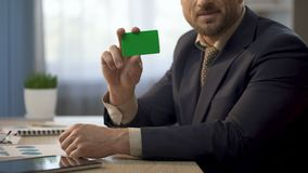 Angestellter, der am Schreibtisch, Karte in der grünen Farbe zeigend, Versicherung sitzt stock video footage