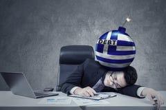 Angestellter mit Bombe der Schuld und der griechischen Flagge stockfotos