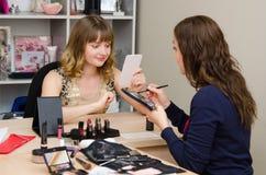 Angestellter schaut im Spiegel auf Make-upberatung Lizenzfreie Stockfotografie