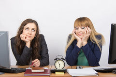 Angestellter zwei im Büro, welches auf das Ende von Arbeitsstunden auf der Uhr wartet Lizenzfreies Stockbild
