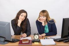 Angestellter zwei im Büro, welches die Uhr betrachtet und auf das Ende der Arbeitszeit wartet Lizenzfreies Stockbild