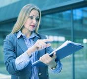 Angestelltfrau, die mit Ordner von Dokumenten steht Lizenzfreie Stockfotos