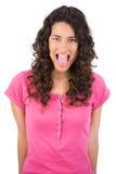 Angewiderter langhaariger Brunette, der heraus ihre Zunge haftet Stockbild