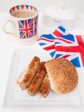 Angielska kiełbasiana kanapka z filiżanką herbata i flaga Zdjęcia Royalty Free