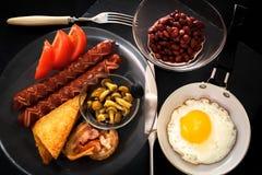 Angielski śniadanie z jajkiem, bekonem, kiełbasami, grzanką, fasolami, pieczarkami, pomidorami i sokiem, jajko smażył target1071_ Obrazy Stock