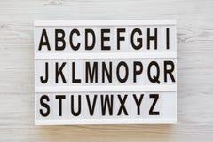 Angielski abecadło na lightbox nad białym drewnianym tłem, zasięrzutny widok Listy od A Z tylna koncepcji do szkoły Od above, zdjęcia royalty free