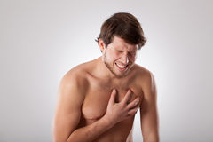Angina. Man isolated suffering from heart disease holding his chest Royalty Free Stock Photography