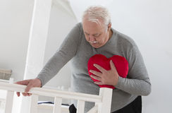 ANGINA PECTORIS SENIOR. Senior man holding an heart symbole of heart attack Royalty Free Stock Photos