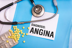 Angina word written on medical blue folder with patient files. Pills and stethoscope on background Royalty Free Stock Photography