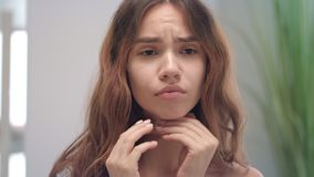 Angine de sentiment de femme de renversement et contact du miroir avant de salle de bains de cou de peau banque de vidéos