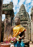 Angkor Buddha. A stone buddha inside the Angkor Wat complex still recieves offerings and is wearing typical buddha dress Stock Photos