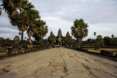 Angkor, Cambodia - December, 2015: Angkor Wat entrance. Picture taken at the entrance of Angkor Wat. The main monument is at the of the path. Palm trees are at Stock Photo