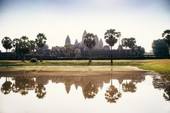 Angkor Vat parmi des palmiers reflétés dans l'eau, Cambodge photo libre de droits