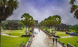 Angkor Wat-largest temple in the world. It is raining. Tourists walk around the temple