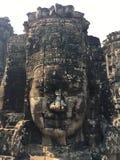Angkor Wat em Siem Reap, Cambodia As caras de pedra cinzelaram nas ruínas antigas do templo do Khmer de Bayon imagens de stock