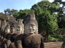 Angkor Wat enfrenta Estátuas dos deuses, cidade antiga asiática, religião velha do khmer imagem de stock
