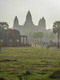 Angkor Wat through morning mist. Towers of ancient temple in the distance seen through the mist stock photos