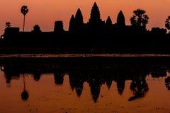 Angkor Wat på soluppgång över sjön, reflekterad i vatten Fotografering för Bildbyråer