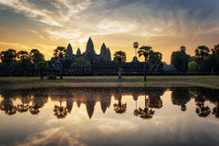 Angkor Wat reflected in lake at dawn. Siem Reap, Cambodia. Mysterious towers of ancient temple complex Angkor Wat at sunrise. Siem Reap, Cambodia. Temple Stock Image