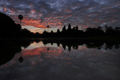 Angkor Wat and red sky reflected in the lake at sunrise, view of popular tourist attraction ancient temple in Siem Reap, Cambodia. Angkor Wat reflected in the stock photo