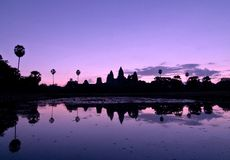 Angkor Wat reflected in silhouette at sunrise. Silhouette of the ruins of Angkor Wat and the surrounding trees reflected in a pond at sunrise stock photos