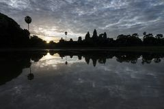 Angkor Wat reflected in water at sunrise, view of popular tourist attraction ancient temple in Siem Reap, Cambodia. Angkor Wat reflected in the lake at sunrise stock images