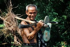 elderly senior khmer man walking home from his farm with some roots and his tool in his hand stock photos
