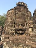 Angkor Wat in Siem Reap, Cambodia. Stone faces carved in the ancient ruins of Bayon Khmer Temple. In jungle forest. Place of worship and popular tourist travel Stock Photos
