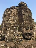 Angkor Wat in Siem Reap, Cambodia. Stone faces carved in the ancient ruins of Bayon Khmer Temple. In jungle forest. Place of worship and popular tourist travel Stock Photo