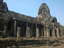 Angkor Wat in Siem Reap, Cambodia. Stone faces carved in the ancient ruins of Bayon Khmer Temple. In jungle forest. Place of worship and popular tourist travel Stock Image