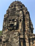 Angkor Wat in Siem Reap, Cambodia. Stone faces carved in the ancient ruins of Bayon Khmer Temple. In jungle forest. Place of worship and popular tourist travel Stock Photography