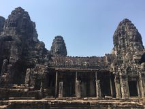 Angkor Wat in Siem Reap, Cambodia. Stone faces carved in the ancient ruins of Bayon Khmer Temple. In jungle forest. Place of worship and popular tourist travel Stock Images