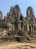 Angkor Wat in Siem Reap, Cambodia. Stone faces carved in the ancient ruins of Bayon Khmer Temple. In jungle forest. Place of worship and popular tourist travel Royalty Free Stock Images