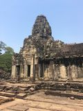 Angkor Wat in Siem Reap, Cambodia. Stone faces carved in the ancient ruins of Bayon Khmer Temple. In jungle forest. Place of worship and popular tourist travel Royalty Free Stock Photo