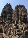 Angkor Wat in Siem Reap, Cambodia. Stone faces carved in the ancient ruins of Bayon Khmer Temple. In jungle forest. Place of worship and popular tourist travel Royalty Free Stock Image