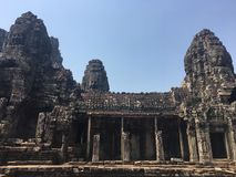 Angkor Wat in Siem Reap, Cambodia. Stone faces carved in the ancient ruins of Bayon Khmer Temple. In jungle forest. Place of worship and popular tourist travel Royalty Free Stock Photography