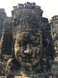 Angkor Wat in Siem Reap, Cambodia. Stone faces carved in the ancient ruins of Bayon Khmer Temple stock images