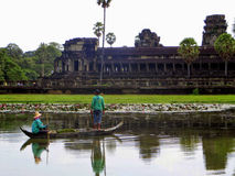 Angkor Wat tempel under dagen som presenterar ett man- och kvinnafiske i ett litet fartyg som ser templet i bakgrunden royaltyfri foto