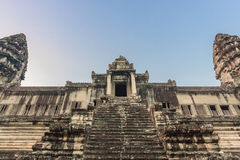 Angkor Wat Temple at sunrise on the blue sky. Beautiful front view. Stairs leading to upper gallery and tower of main. Stairs leading to upper galleries and Royalty Free Stock Image