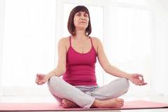 Angle faible de femme harmonieuse détendant tout en faisant la pose de yoga dedans Photo stock