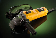 Angle grinder. Yellow angle grinder with protective glass over green background Stock Images