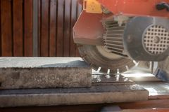 An angle grinder or circular saw with a concrete block Stock Photos