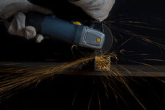 Angle grinder cutting a metal square tube making shower of spark Stock Images