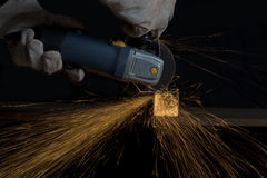 Angle grinder cutting a metal square tube making shower of spark Royalty Free Stock Photography