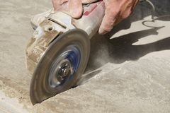 Angle Grinder Cutting or Scoring Concrete. An angle grinder with a diamond blade scoring concrete Royalty Free Stock Photos