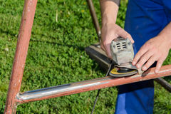 Angle grinder, metal structure renovation. In a garden Royalty Free Stock Photography