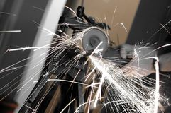 Angle grinder in use, cutting pipes for waterwork Royalty Free Stock Photography