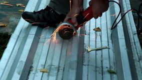 Angle grinder. A worker cuts a piece of metal into two parts with an angle grinder stock video footage