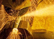 Angle grinder working. On a metal tube clamped in a vise Stock Photos